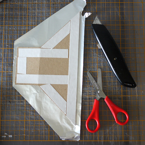 4. Lay out the card on the foil and apply double-sided tape
